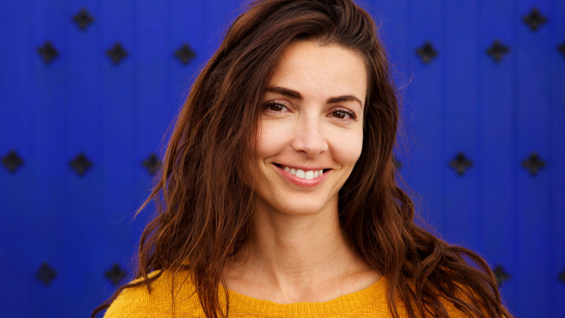 Close up portrait of beautiful young woman smiling against blue background