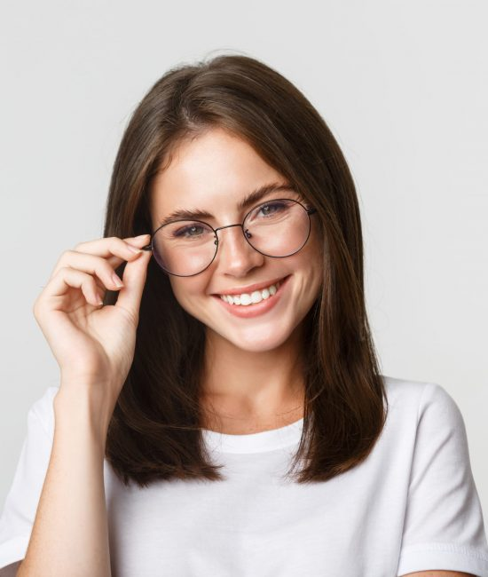 Close-up of smiling confident, beautiful brunette girl in glasses looking happy.