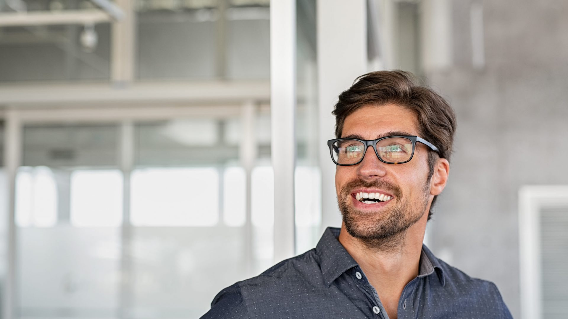 Confident young businessman looking up with big grin. Happy handsome business man wearing spectacles looking away in modern office. Close up face of smiling  guy having idea. Man dreaming of success and pondering new startup.