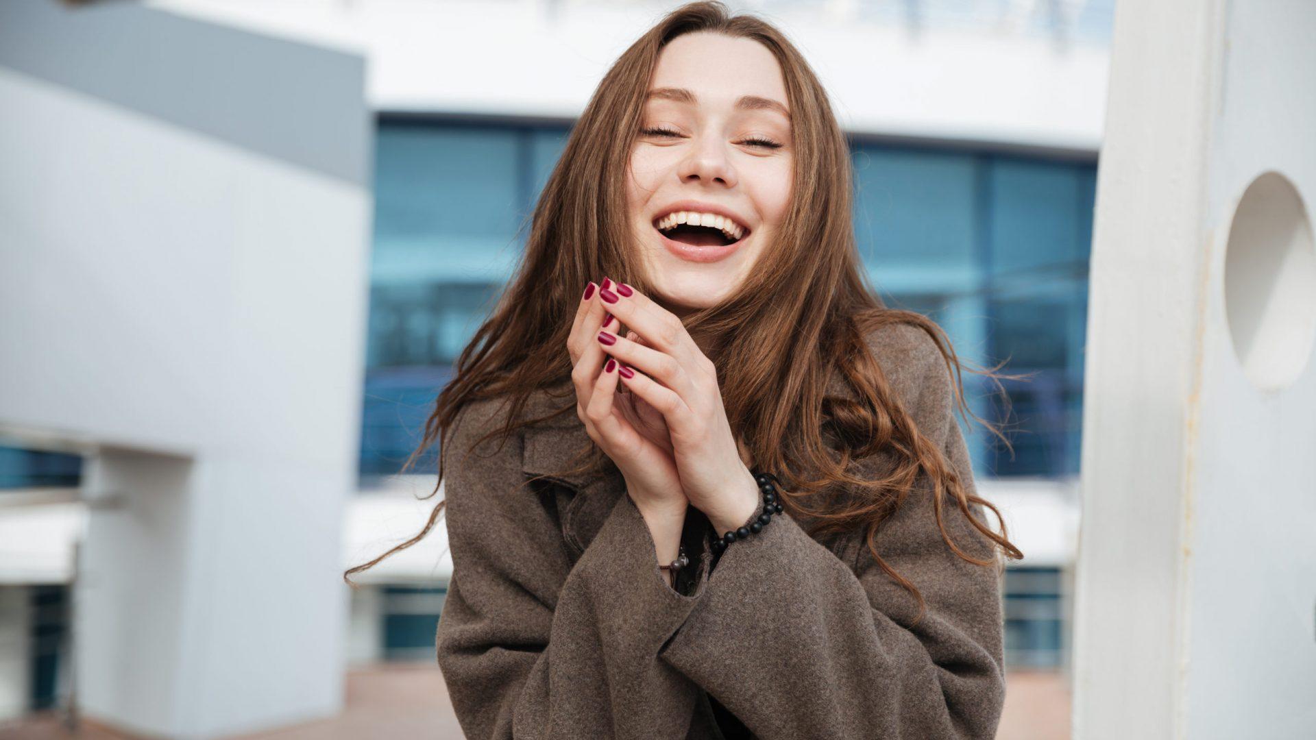 Brunette woman in coat laughing and enjoying walking