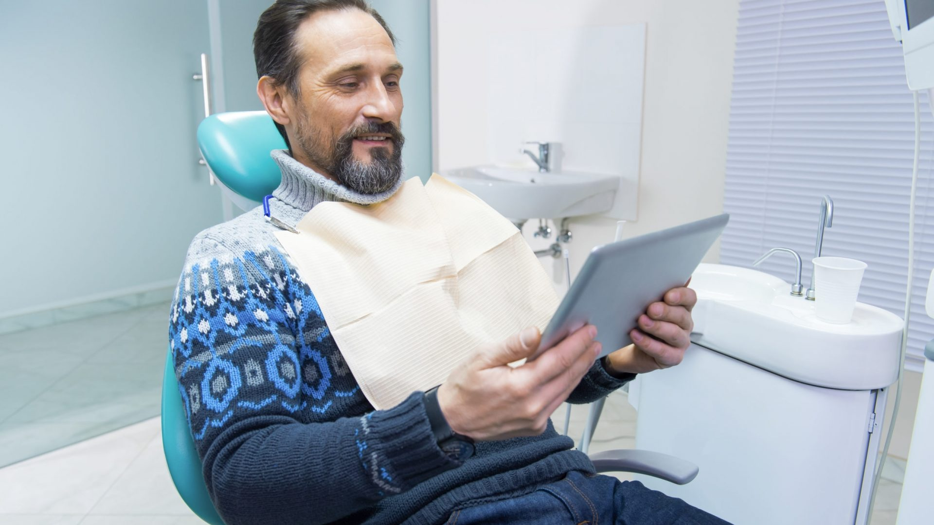 Man sitting in dentist chair. Mature guy looking at tablet.